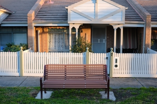 A park bench installed on the nature strip front of a row of houses