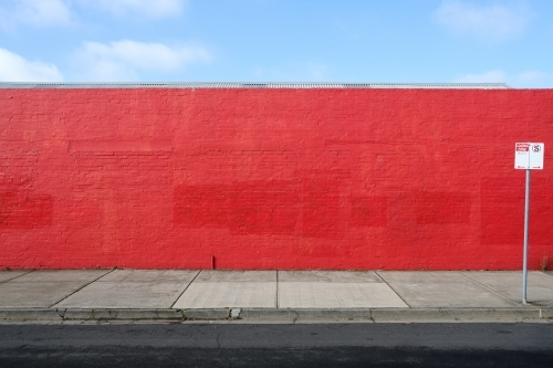 A long red wall with a street sign in front of it
