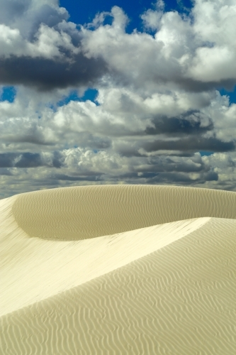 Large sand dunes and ripples under a summer sky