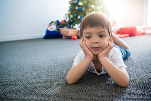 Cute mixed race 4 year old boy waiting for Christmas