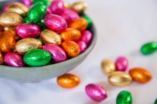 Colorful, foil wrapped Easter eggs in a bowl on white