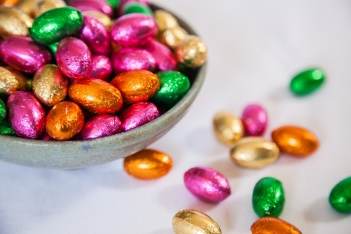 Colourful, foil wrapped Easter eggs in a bowl on white