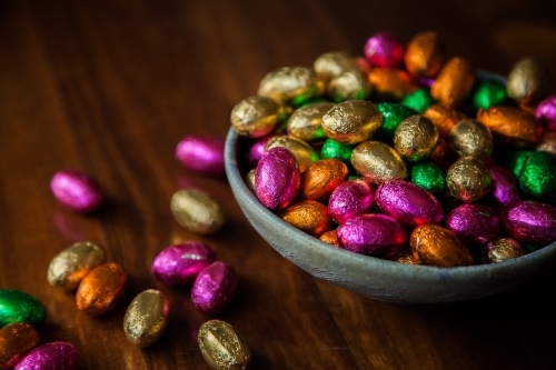 Bowl of colourful chocolate Easter eggs on wood