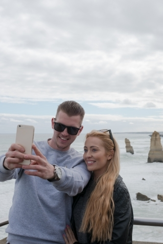 Young couple taking selfies with the 12 Apostles in the background