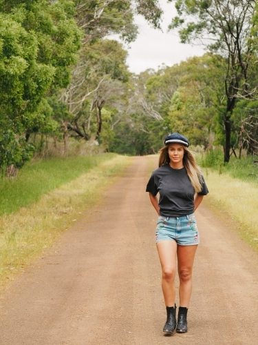 Mid twenties country girl walking down a bush track.