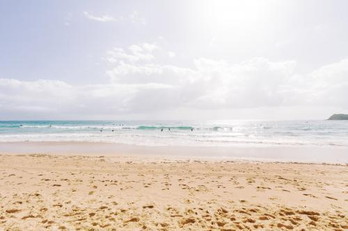 Walked in sand on Bondi Beach and surf with sun flare