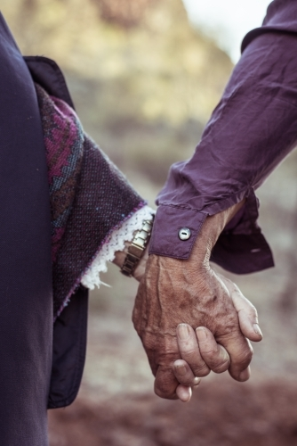 Elderly couple holding hands