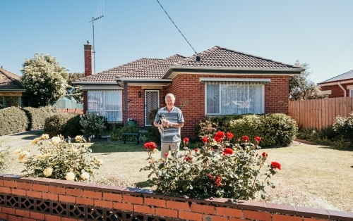 Elderly man and his dog in front of his red brick home.