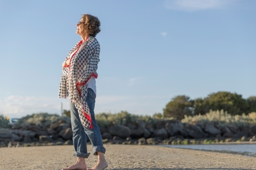 Elderly middle eastern woman standing on beach