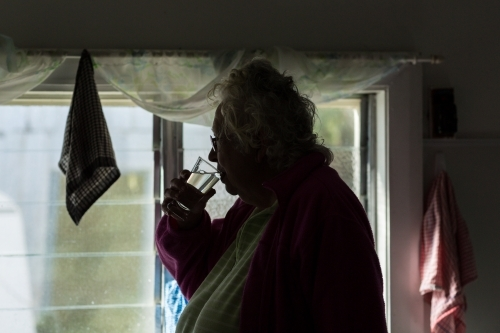 Elderly woman in dim room drinking water