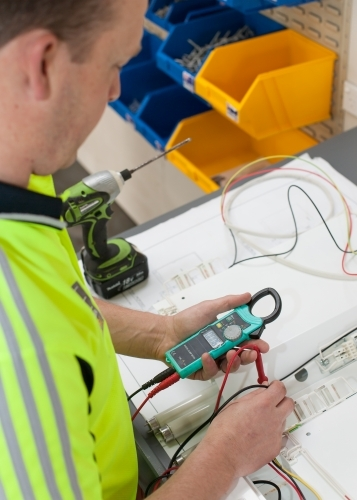 Electrician testing current with a multimeter