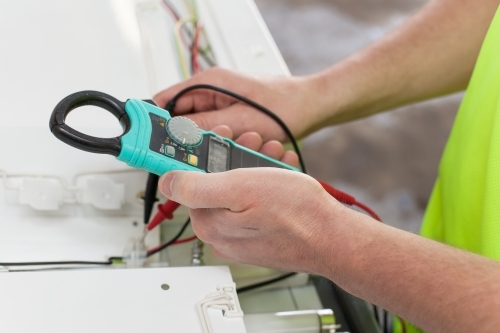 Electrician testing power board with a multimeter