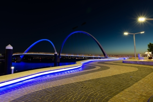 Evening view of arched bridge against blue evening sky with leading lines of blue lights and pavers