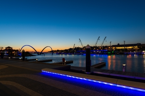 Evening view of Elizabeth Quay with arched bridge against orange glow of sunset and reflected lights
