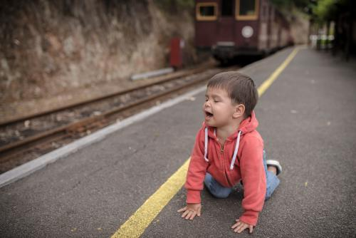 Excited 2 year old mixed race boy on hands and knees an a train platform