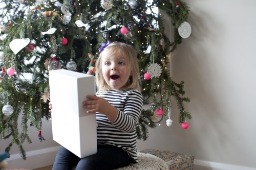 Excited young girl with present in front of Christmas tree
