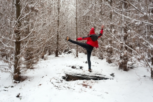 Exercising and stretching in the snow while balanced on log