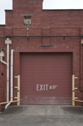 EXIT sign on old red door of warehouse