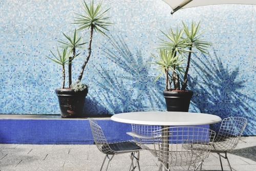 Exterior of table, chairs and plants by pool