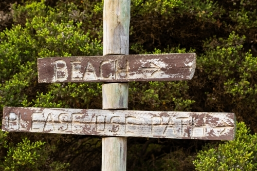 Faded rustic wooden sign pointing to beach