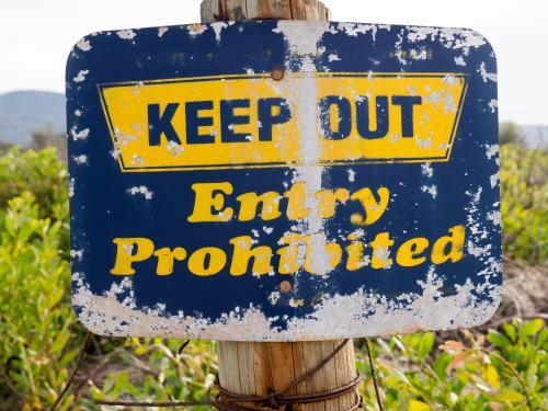 "A well worn ""KEEP OUT Entry Prohibited"" blue and yellow sign"