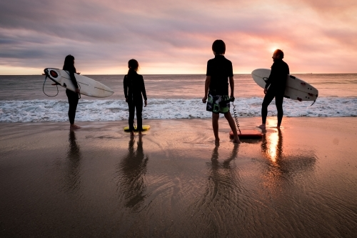 Family of four standing on beach in silhouette holding surfboards with moody  sunset