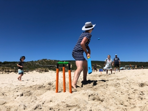 Family playing cricket at the beach in the sand