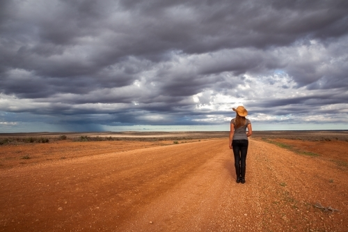 Farm woman watches the storm over an arid desert landscape outback Australia