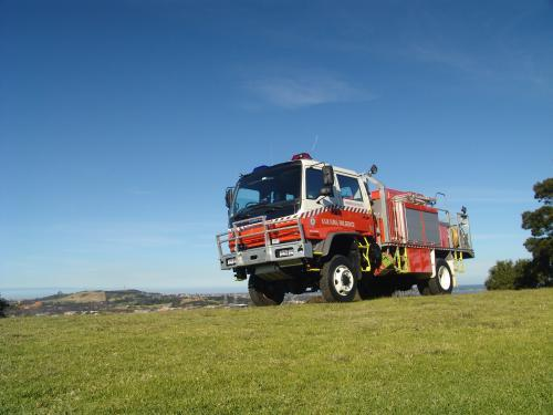 Fire truck on a green hilltop against a blue sky