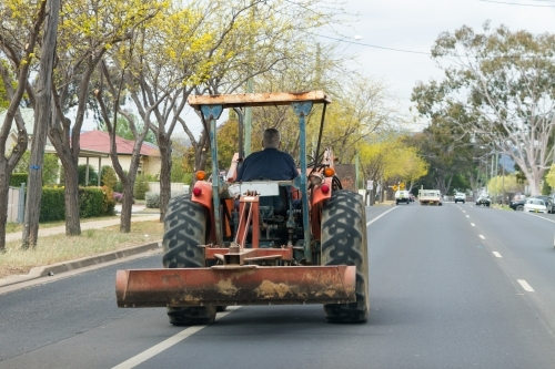 Farmer driving his tractor down the main street of a country town