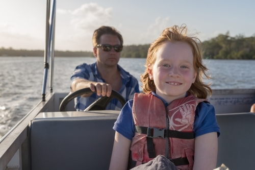 father and daughter steering a boat together
