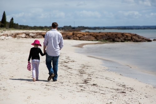Father and daughter walk hand in hand along a beach
