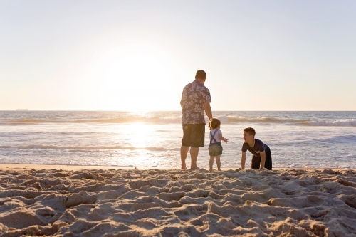 Father And His Two Children At The Beach At Sunset