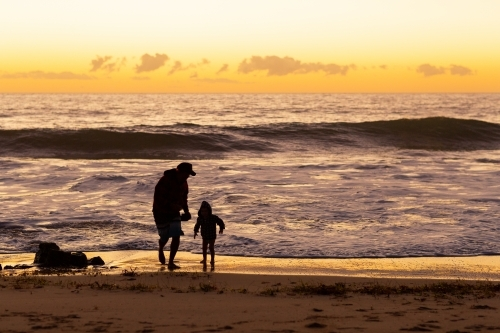 Father and son at the seashore at sunset