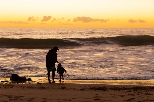 Father and son play at the water's edge at sunset