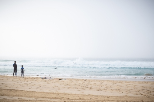 father and son surfers enjoy the waves and dense fog