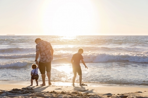 Father and Two Children Playing On the Shoreline At Sunset