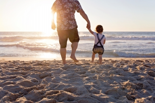 Father And Young Child Holding Hands On The Beach At Sunset
