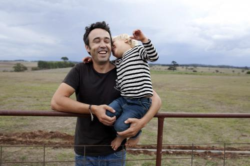 Father and young son laughing together on old gate on rural farm