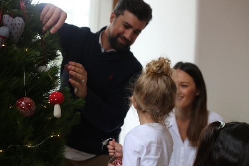 Father, mother and daughter decorating Christmas tree