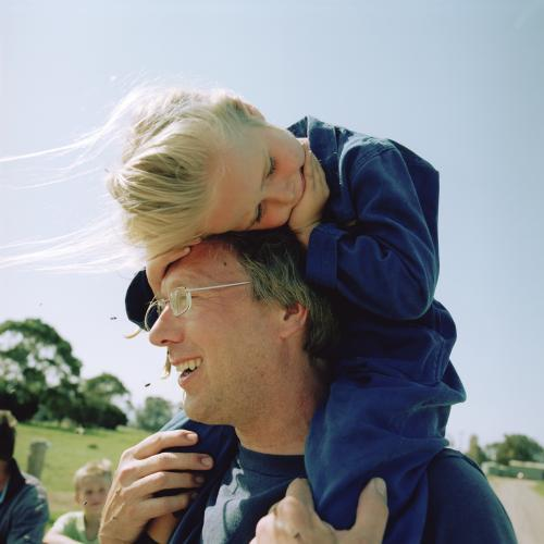 Father with daughter on shoulders on the farm