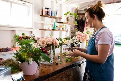 Female florist preparing wedding suit buttonholes at a work bench full of vases of flowers