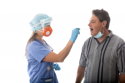Female healthcare worker swabs a man for infectious disease such as SARS or COVID-19 or influenza