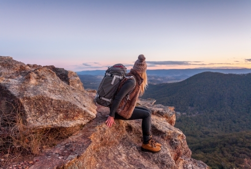 Female hiker with backpack rests on a mountain peak rocky ledge in Blue Mountains Australia