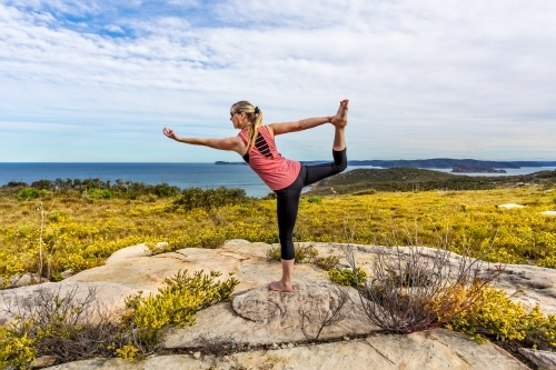 Female in outdoor coastal setting with wildflowers blooming doing yoga