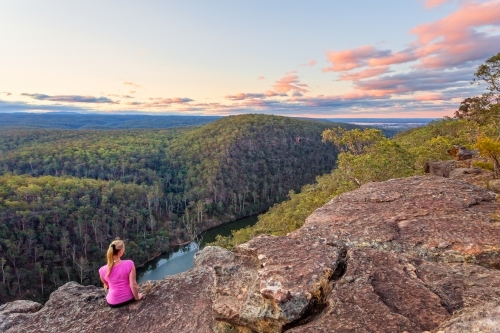 Female sitting on a rocky cliff with views over the Nepean Gorge and Blue Mountains, Australia