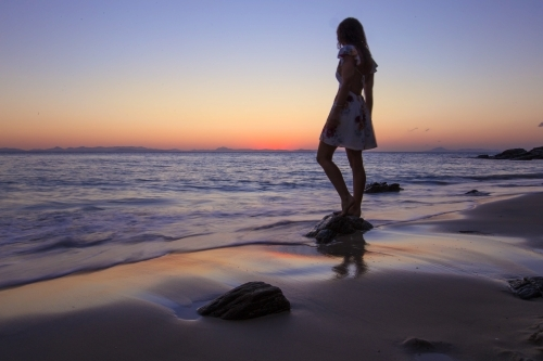 Female standing on Rock at the beach at Sunset