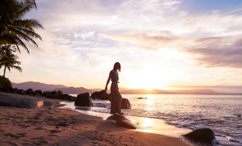 Female standing on rock at the beach with sunset skies