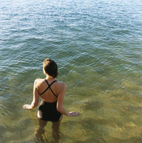 Female swimmer from behind standing in waist deep water