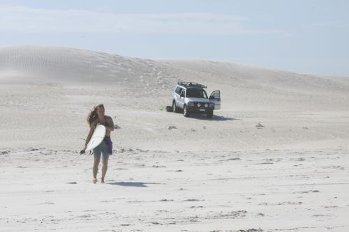 Female walking on sand dunes to head out for a surf